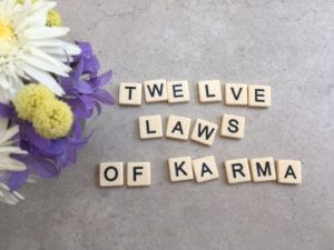 Twelve laws of Karma written in scrabble letters.